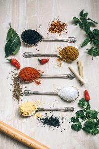 Picture of salt and dried herbs and spices on spoons.
