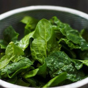 Raw spinach in a colander